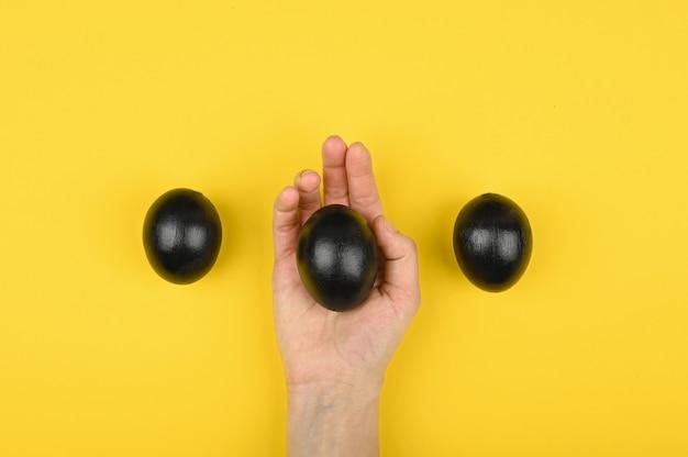 Das schwarze ei liegt in der hand. auf gelbem grund. die wohnung lag. schwarzes ostern. drei schwarze eier