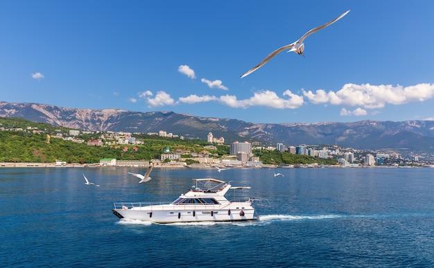 Das schwarze meer und ein boot in der nähe der küste von jalta, krim.