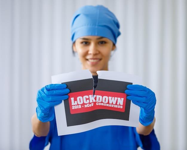 Das schwarze und rote coronavirus 2019 ncov lockdown-papierschild wurde von einem glücklichen, schönen arzt in blauer krankenhausuniform auf verschwommenem hintergrund auseinandergerissen, als das normale leben der coronavirus-pandemie wieder endet.