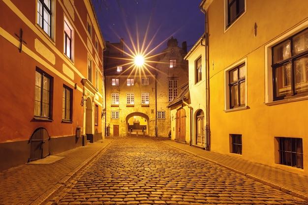 Das schwedische tor, teil der alten rigaer mauer, und typische europäische mittelalterliche straße bei nacht, riga, lettland
