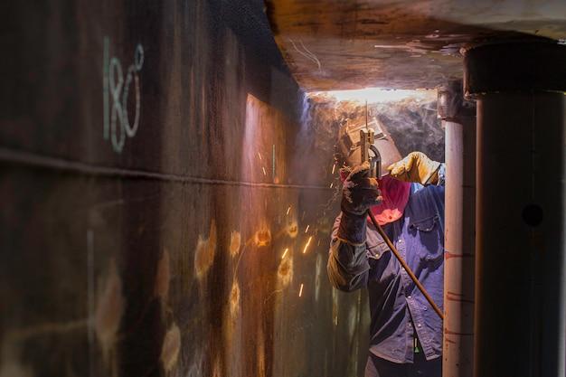 Das schweißen des männlichen arbeitermetallbogens ist teil des maschinentankdüsen-pipelinebaus erdöl- und gaslagertanks in engen räumen.