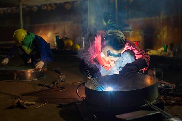 Das schweißen von männlichem arbeitermetall ist teil des baus von erdöl- und gaslagertanks für maschinentankdüsen in engen räumen.