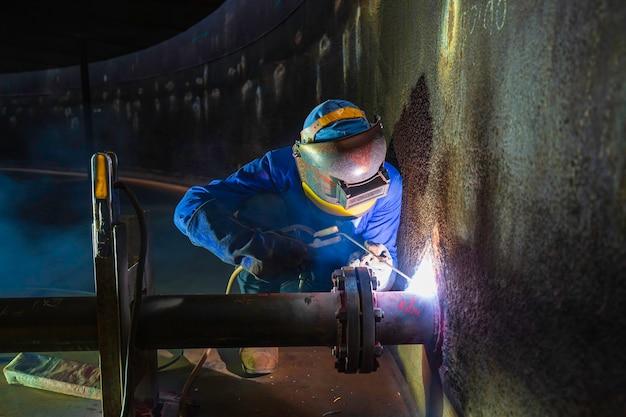 Das schweißen von männlichem arbeitermetall ist teil des baus von erdöl- und gasspeichertanks für maschinentankdüsen in engen räumen.