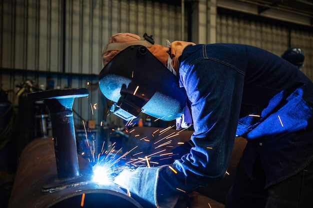 Das schweißen von männlichem arbeitermetall ist teil des maschinendüsen-pipelinebaus erdöl und erdgas