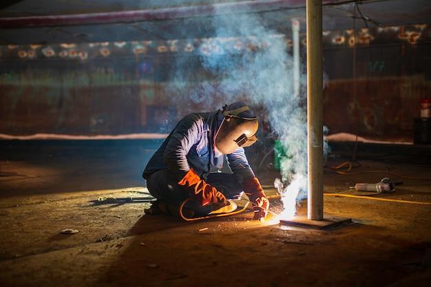 Das schweißen von männlichem arbeitermetall ist teil des tankplattenbodenaufbaus für erdöl- und gaslagertanks in geschlossenen räumen.