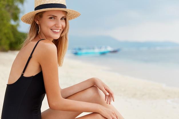 Das seitliche porträt der glücklichen demale sitzt auf heißem sand, trägt einen badeanzug, einen strohhut, bewundert den herrlichen meerblick und genießt eine ruhige atmosphäre, sieht wunderschön aus, trägt einen sommerhut und einen badeanzug
