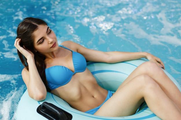 Das sexuelle mädchen, das im schwimmbad sitzt