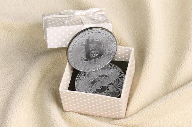Das silberne bitcoin liegt in einer kleinen orangefarbenen geschenkbox mit einer kleinen schleife auf einer decke aus weichem und flauschigem hellorangeem fleece