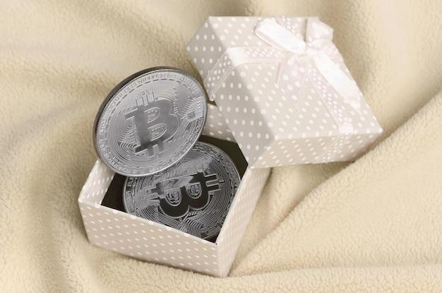 Das silberne bitcoin liegt in einer kleinen orangefarbenen geschenkbox mit einer kleinen schleife auf einer decke