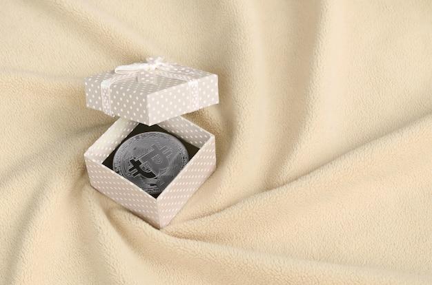 Das silberne bitcoin liegt in einer kleinen orangefarbenen geschenkbox mit kleiner schleife