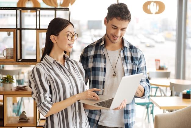 Das sind neue lösungen. lächelnde junge asiatische frau, die mit laptop nahe ihrem männlichen gefährten steht und wichtige momente bespricht.