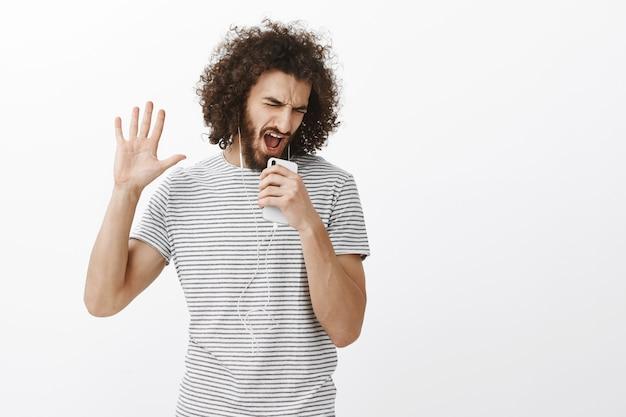 Das singen wurde zu lebenstexten. porträt des freudigen ausdrucksstarken attraktiven mannes mit bart und lockigem haar