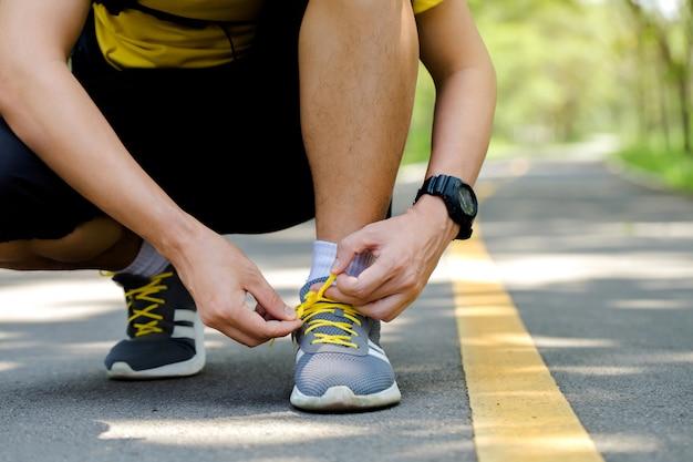 Das sitzen des jungen mannes bindet ihre schuhe, bevor er rüttelt und der läufer, der die spitzee im freien bindet.