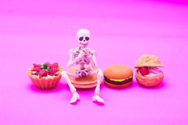 Das skelett sitzt auf einer bäckerei und genießt es, bis zum tod mit süßen desserts zu essen.