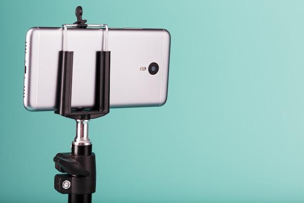 Das smartphone ist als foto-video-kamera für ein blog auf blauem hintergrund auf einem stativ montiert. nehmen sie videos und fotos auf.