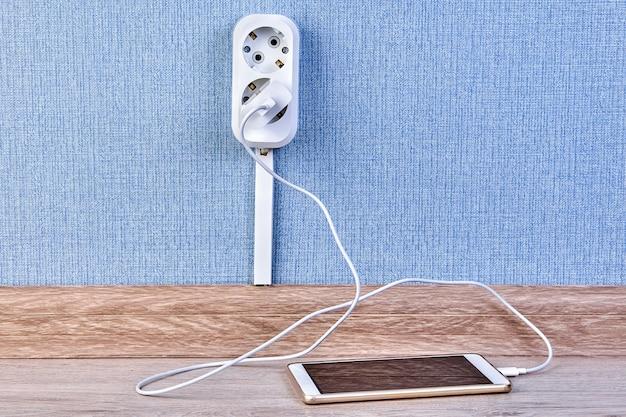Das smartphone ist an ein ladegerät angeschlossen, das in eine doppelte steckdose eingesteckt ist.