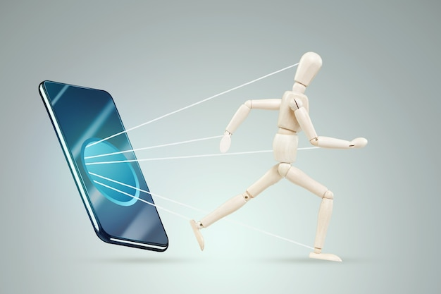 Das smartphone saugt eine figur eines marionettenmannes ein. das konzept der smartphone-sucht, moderne probleme, das leben im internet, sozial. netzwerke.