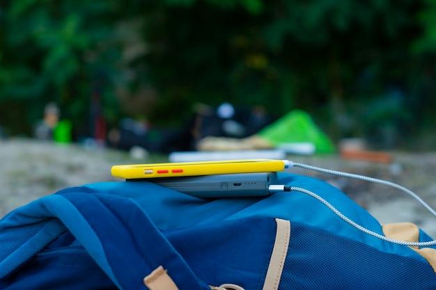 Das smartphone wird mit einem tragbaren ladegerät aufgeladen. power bank lädt das telefon im freien mit einem rucksack für den tourismus in der natur auf.