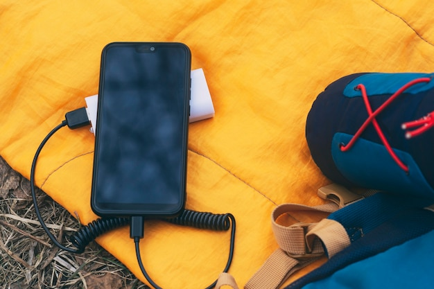 Das smartphone wird mit einem tragbaren ladegerät aufgeladen. powerbank mit handy auf einem schlafsack mit rucksack.