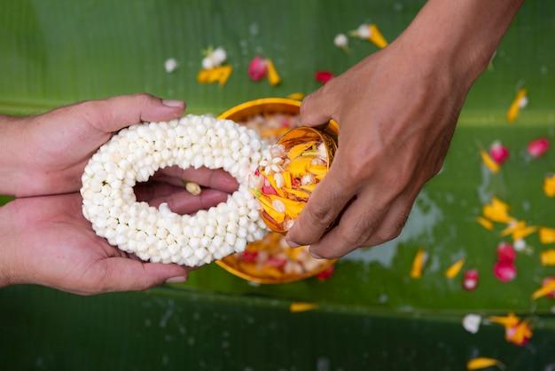 Das songkran festival und die thailändische neujahrsserie geben thailändische ältere jasmingirlanden und segen von älteren verwandten