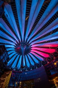 Das sony center am potsdamer platz wird nachts in berlin beleuchtet.