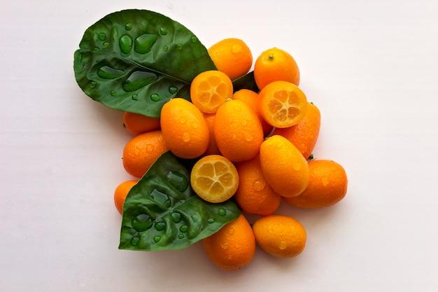Das spa besteht aus einem satz mandarinenblätter und einer kerze. weißer hintergrund. kopieren sie platz.