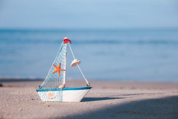 Das spielzeug-segelboot liegt in der morgensonne am strand. reisekonzept für den sommerurlaub