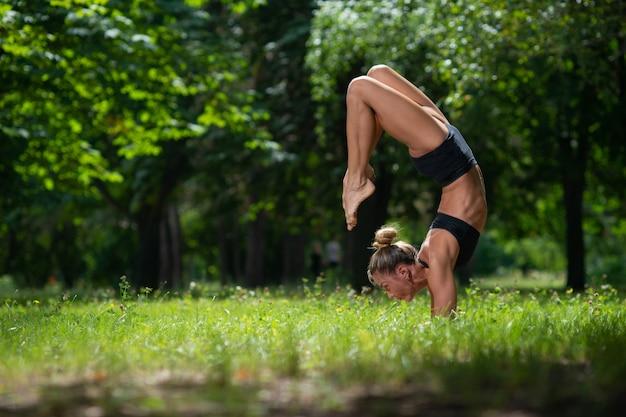 Das sportliche akrobatmädchen, das auf ihren händen steht, führt ein akrobatisches element durch