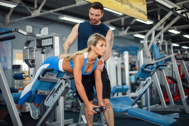 Das sportliche mädchen, das gewicht tut, trainiert mit unterstützung ihres persönlichen trainers an der turnhalle.