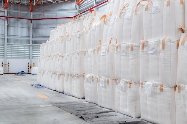 Das stapeln von schüttgut in jumbo-säcken wird im lagerhaus gelagert.