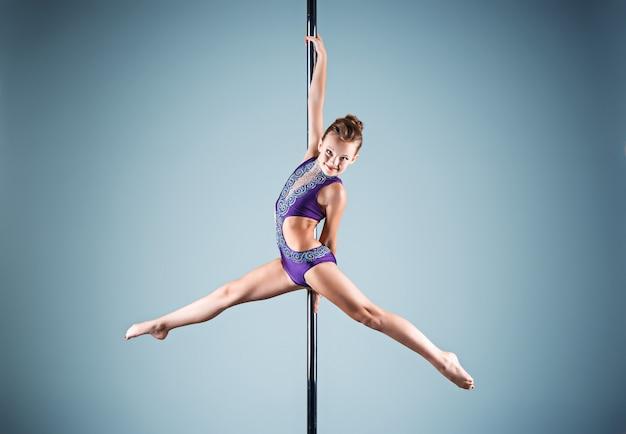 Das starke und anmutige junge mädchen, das akrobatische übungen auf pylon durchführt