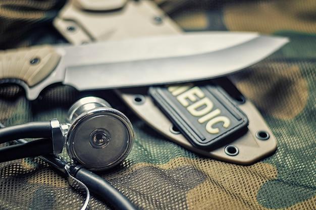 Das stethoskop liegt auf der uniform eines soldaten. das konzept der gesundheitsversorgung, der militärversicherung und der staatlichen versorgung.