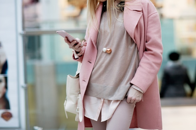Das stilvolle junge mädchen, das in einem rosa mantel in einem shop steht und untersuchen das telefon