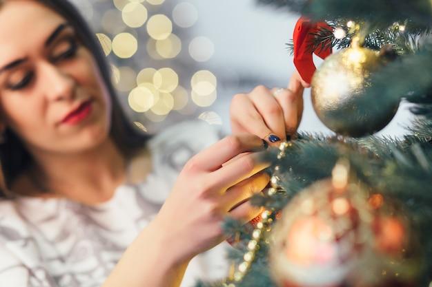 Das stilvolle mädchen, das einen weihnachtsbaum verziert