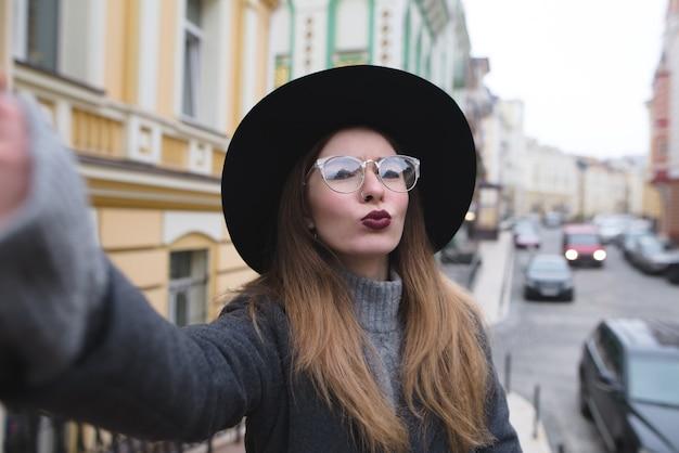 Das stilvolle mädchen nimmt selfie-straße, während es durch die schöne stadt geht.
