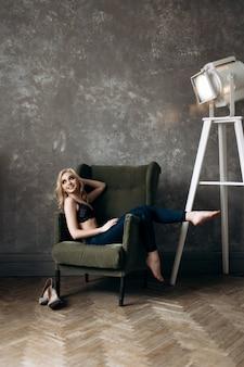 Das stilvolle mädchen sitzt auf dem stuhl