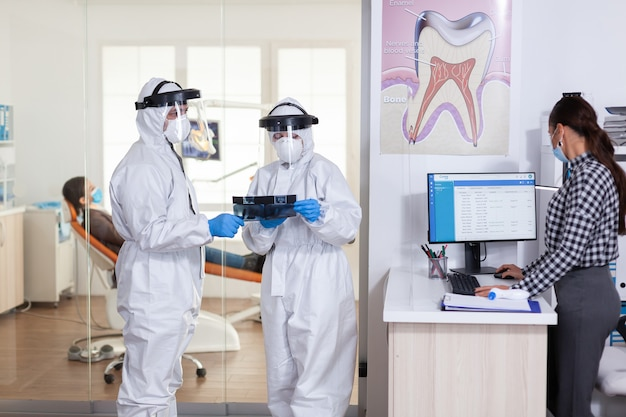 Das stomatologie-team, das während der globalen pandemie mit coronavirus in der zahnärztlichen rezeption in einem ppe-anzug gekleidet war, hält eine röntgenaufnahme des patienten und hält die soziale distanz aufrecht