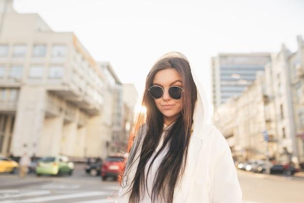 Das straßenporträt eines attraktiven mädchens trägt eine sonnenbrille und eine weiße jacke, steht bei sonnenuntergang auf dem hintergrund einer stadtlandschaft, schaut in die kamera und lächelt