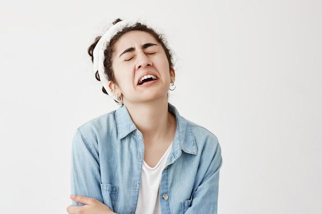 Das stressige, verwirrte junge weibliche model mit dem dunklen, welligen haar trägt einen lappen und ein jeanshemd, die in panik sind, da es nicht weiß, was es mit einem freund, einem besorgten, stirnrunzelnden gesicht und weinen anziehen soll.