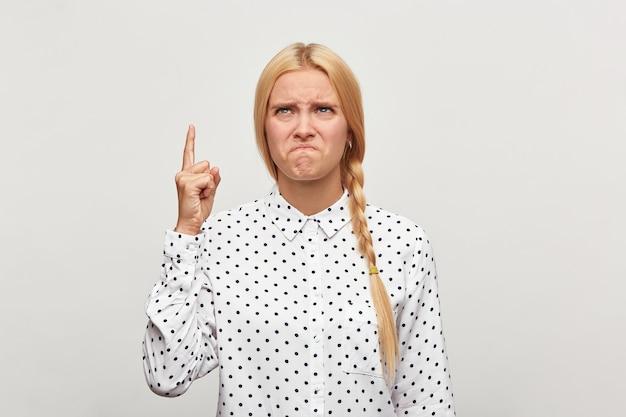 Das studioporträt einer blonden jungen frau mit haaren, die in einem geflochtenen, frustrierten, verzweifelten aufruhr versammelt sind, zeigt die gespitzten lippen des fingers
