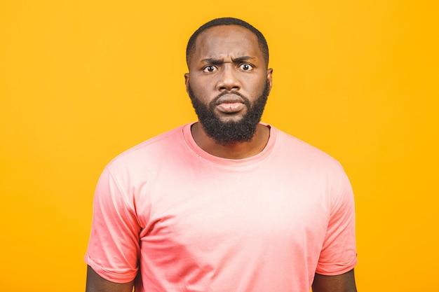 Das studioporträt über dem gelben leeren isolierten dunkelhäutigen traurigen mann, der weißes t-shirt trägt, fühlt sich frustriert und unglücklich