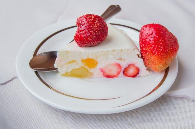 Das stück dessert mit erdbeeren und sahne auf einem tellerlöffel