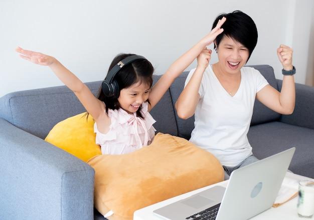 Das süße asiatische mädchen und ihr lehrer verwenden ein notizbuch zum lernen des online-unterrichts während der quarantäne zu hause. online-bildung und soziales distanzkonzept.