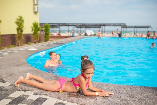 Das süße kleine mädchen im rosafarbenen badeanzug liegt am rand des pools und sonnt sich an einem sonnigen sommertag im urlaub unter den hellen sonnenstrahlen. tourismus- und reisekonzept. platz für werbung