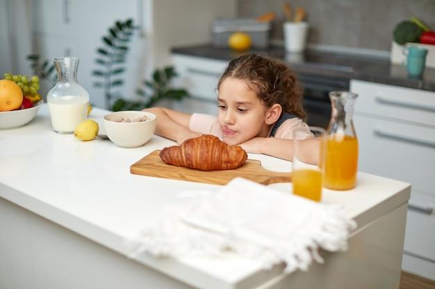 Das süße kleine mädchen mit dem lockigen haar betrachtete ein köstliches croissant am küchentisch.