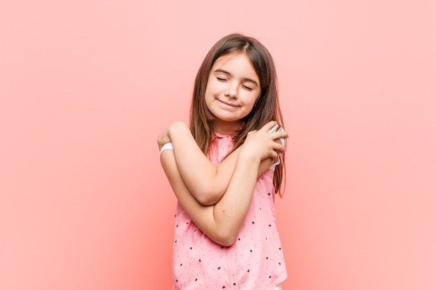 Das süße kleine mädchen umarmt sich und lächelt sorglos und glücklich.