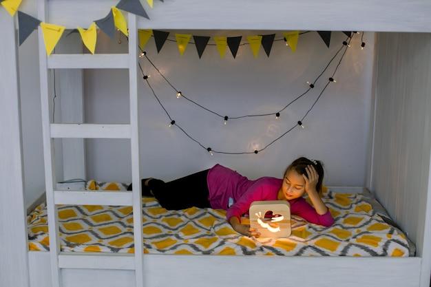 Das süße mädchen ist bereit, im bett zu schlafen. abend nacht. kleines mädchen, das auf stilvollem dekoriertem etagenbett liegt und die hölzerne nachtlampe betrachtet.