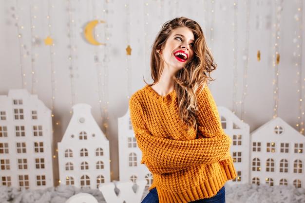 Das süße model lacht aufrichtig in warmer atmosphäre. schöne landschaft im zimmer macht mädchen glücklich