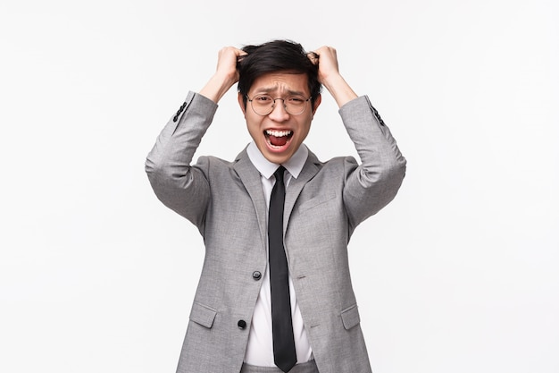 Das taillenporträt eines alarmierten und verlegenen jungen asiatischen männlichen büroleiters kann die frist nicht einhalten, machte einen großen fehler und zog sich gestresst die haare aus dem kopf