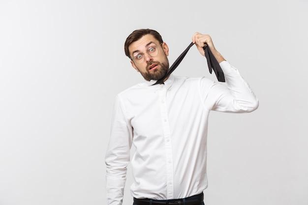 Das taillenporträt eines gelangweilten oder müden kaukasischen jungen büroleiters hat es satt, sich unwohl zu fühlen, sich an die krawatte zu hängen und selbstmord zu imitieren